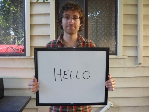 Man holding sign saying hello