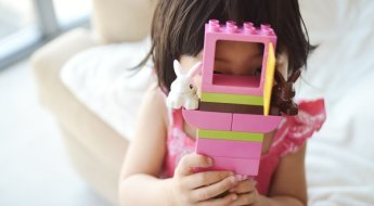 Annie-Tao-Photography-Photographing-Shy-Kids-girl-hiding-behind-Legos.jpg