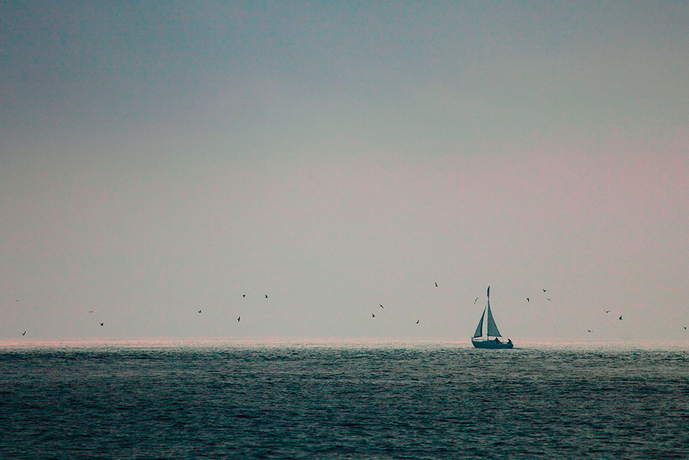 In this image, I had a flat gray mist killing any interest in the sky.  But when this lone sailboat began sailing right at the edge of the mist, I began to see possibilities.  By placing the sailboat at the intersection of the rule of thirds, and placing the horizon line at the bottom third of the image, I allowed the negative space to take up a lot of room.  That negative space gives the boat a place to go, and keeps the interest squarely on the sailboat.
