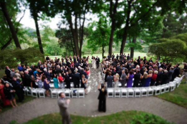 One of the things I'll do is set up a remote camera in the back of the ceremony, elevated if possible.  In this shot, a tilt-shift lens was used to create that miniature look.  EOS 5D Mark III, TS-E 17mm f/4L. Exposure was 1/320, ISO 3200, f/4.