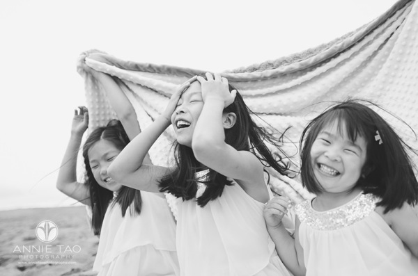 Annie Tao Photography San Francisco Bay Area lifestyle family beach photography three sisters laughing under a blanket BxW