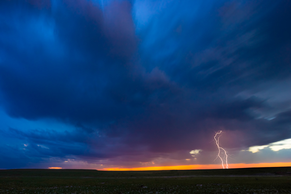 A CG (cloud to ground) lightning bolt strikes in a field somewhere in east Texas as a storm moves off in the distance.
