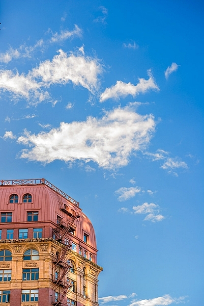 By cropping the building quite aggressively, the image seems unfinished, but the colours and the sky make it work