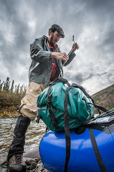 Securing well-sealed dry bags to the front of a packraft, a daily chore on a remote river trip.