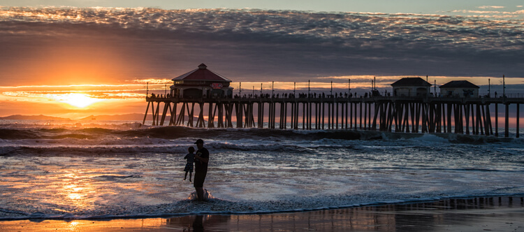 This image tells a story of a Father and son playing in the surf at sunset. The sillouhetted figures add drama to an image that could just be another sunset at the beach.