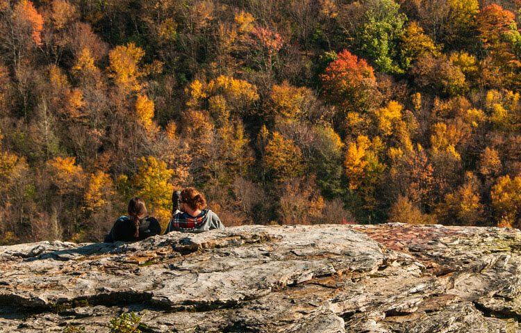 A couple sitting on a rock enjoying the Autumn view adds a romantic drama to the fall colors of the West Virginia Mountains
