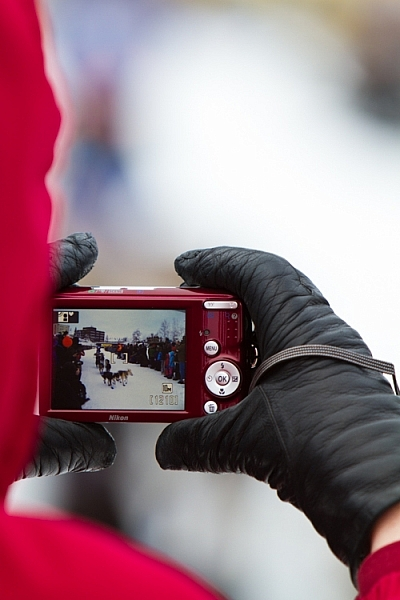 Here, the scene of the dog teams seen through a spectator's camera is more telling of the experience of the start of the Yukon Quest.
